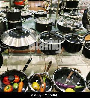 New pans on the shelf in the store - Stock Photo