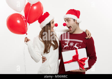 Christmas Concept - Young caucasian couple holding gifts,champagne and balloon making funny face on Christmas - Stock Photo