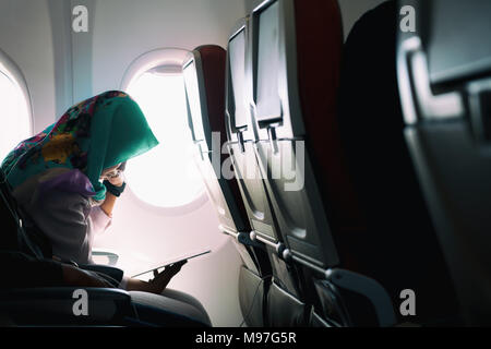 Female lonely muslim traveling on plane while reading on seats during a sunset, lowlight ambience mode - Stock Photo