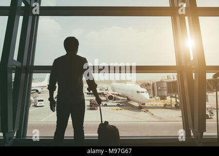 Back side of traveler boy in termainal at airport looking at the flying plane above airport, travel and vacation lifestyle concept - Stock Photo