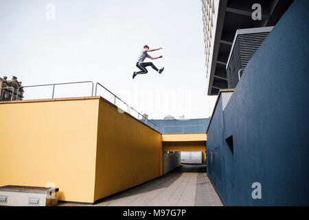 Freerunner is jumping beween colourful buildings in the city. - Stock Photo