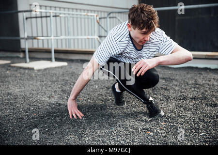 Freerunner is landing on gravel after jumping from a rooftop. - Stock Photo