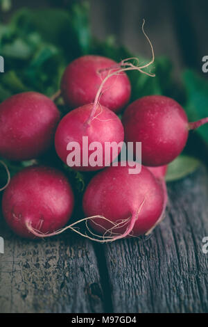 Branch of fresh radish over old boards. The concept of a harvest and organic food. Copy space. Rustic style. - Stock Photo