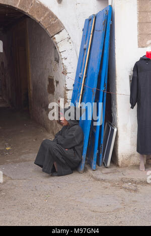 Elderly man in black Berber coat squatting at arched entrance. - Stock Photo
