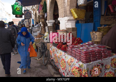 Woman in local dress walking past strawberry fruit stall - Stock Photo