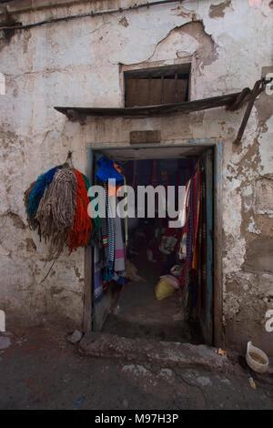 Door in dark alleyway leading into weaver's workshop. - Stock Photo