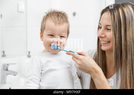 Happy mother teaching her son how to bush teeth in the bathroom - Stock Photo
