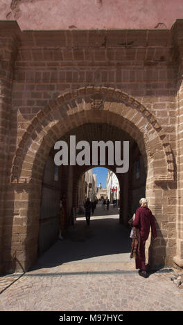 Woman in traditional dress walking towards arched entrance 'Bab Sbaa' in old wall. - Stock Photo