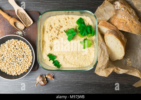 Hummus or houmous, appetizer made of mashed chickpeas with tahini, lemon, garlic, olive oil, parsley, cumin on wooden table - Stock Photo