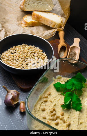 Hummus or houmous, appetizer made of mashed chickpeas with tahini, lemon, garlic, olive oil, parsley, cumin and cedar nuts on wooden table - Stock Photo