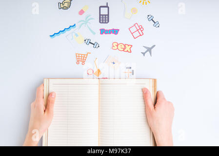 Top view croped female hands holding opened personal organizer and colourful icons of actions on white background. Creative concept image of planning  - Stock Photo