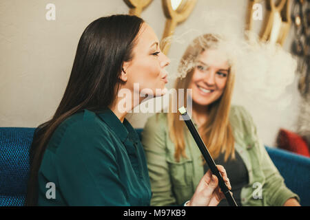 Two happy women are sitting in shisha bar and smoking nargile - Stock Photo