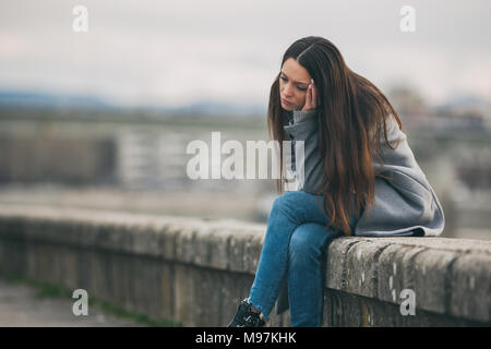 Young lonely and depressed woman is sitting in grief. - Stock Photo