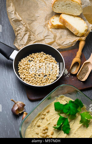 Hummus or houmous, appetizer made of mashed chickpeas with tahini, lemon, garlic, olive oil, parsley, cumin and cedar nuts on wooden table. Healthy lifestyle and eating right concept - Stock Photo
