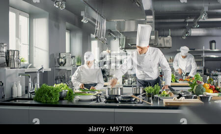 Famous Chef Works in a Big Restaurant Kitchen with His Help. Kitchen is Full of Food, Vegetables and Boiling Dishes. - Stock Photo