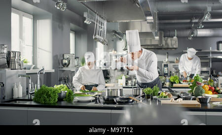 Famous Chef Works in a Big Restaurant Kitchen with His Help. Kitchen is Full of Food, Vegetables and Boiling Dishes. He is trying taste. - Stock Photo