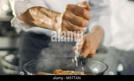 Professional Chef Squeezes Lemon Juice onto Hot Pan with Red Fish Fillet on it. He Works in a Modern Kitchen. - Stock Photo