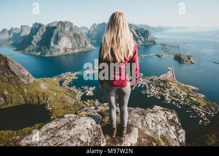 Young blonde woman standing alone on cliff mountain travel lifestyle exploring concept adventure outdoor summer vacations in Norway - Stock Photo