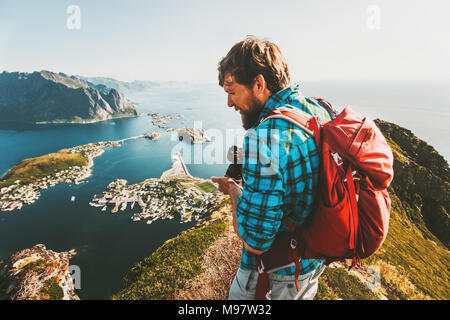 Man traveler with backpack and photo camera sightseeing view from  Reinebringen mountain in Norway lifestyle adventure traveling outdoor summer vacati - Stock Photo
