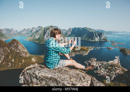 Man traveler using smartphone sitting on cliff edge Travel lifestyle concept adventure outdoor summer vacations in Norway mountains aerial view Lofote - Stock Photo