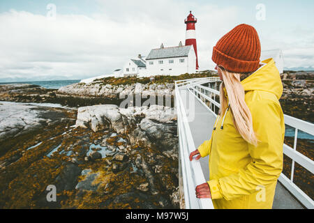 Woman sightseeing Norway lighthouse landscape Travel Lifestyle concept adventure tourist at vacations outdoor girl wearing yellow raincoat standing al - Stock Photo