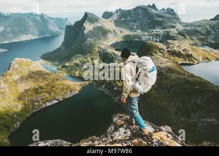 Discoverer man standing on cliff mountain in Norway Traveling lifestyle adventure concept hiking active summer vacations outdoor aerial view - Stock Photo