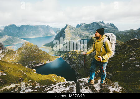 Bearded man traveler standing on cliff mountain in Norway Traveling with backpack healthy lifestyle adventure concept hiking active summer vacations o - Stock Photo