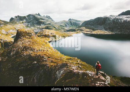 Woman alone with backpack hiking on mountain ridge Traveling lifestyle adventure concept active vacations in Norway outdoor lake aerial view - Stock Photo