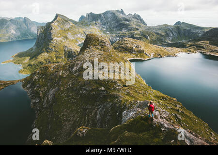 Traveler alone with backpack hiking on mountain ridge landscape hiking Traveling lifestyle adventure concept active vacations in Norway outdoor aerial - Stock Photo