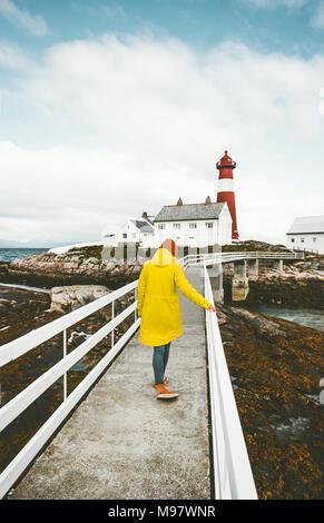 Traveler woman walking on bridge at Norway lighthouse Travel Lifestyle concept adventure scandinavian vacations outdoor - Stock Photo