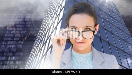 Businesswoman wearing glasses and Tall buildings with economic finance background - Stock Photo
