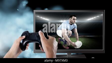 Hands holding gaming controller  with rugby player on television - Stock Photo