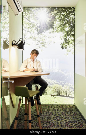 Businessman writing in book at table in modern office with panorama window - Stock Photo