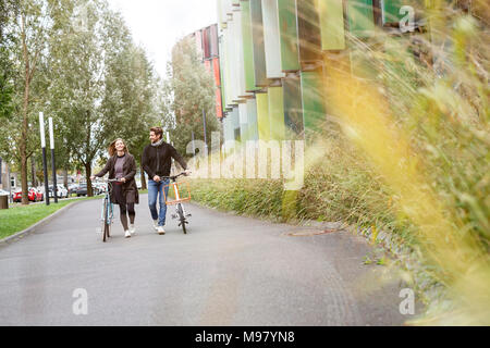 Smiling couple walking with bicycles on a lane - Stock Photo
