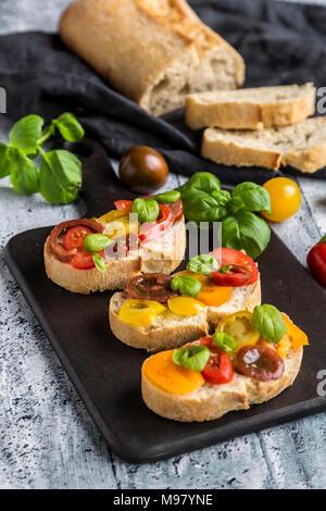 Bruschetta, ciabatta with multi-coloured tomatoes and basil - Stock Photo