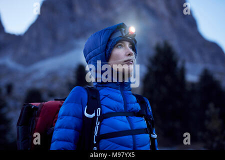 Young woman wearing headlamp at dusk in the mountains - Stock Photo