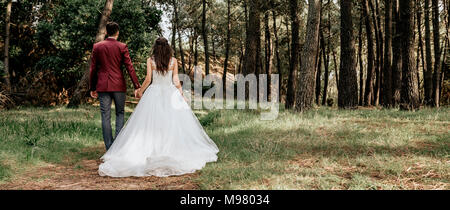 Back view of bride and groom walking in forest - Stock Photo