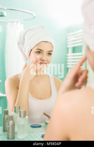 Young woman applying facial moisturizer at mirror in bathroom - Stock Photo