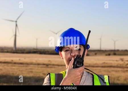 Female technician using walkie-talkie on a wind farm - Stock Photo