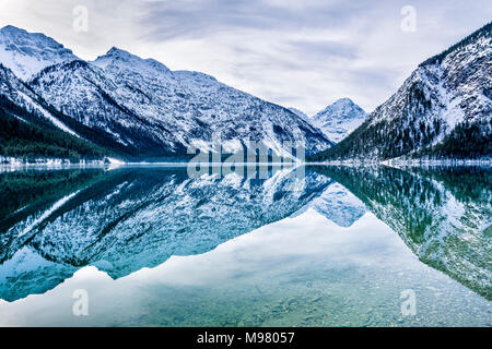 Austria, Tyrol, Ammergau Alps, Lake Plansee in winter - Stock Photo