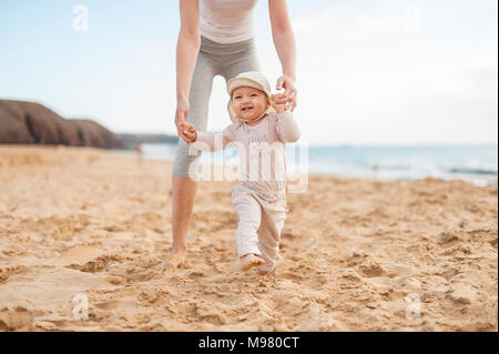Mother helping little daughter walking on the beach