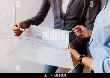 Female architects working on a project, looking at blueprint - Stock Photo