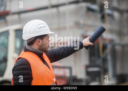 Man wearing safety vest and helmet at construction site - Stock Photo