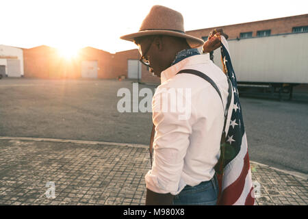 Young man wearing hat and sunglasses holding American flag - Stock Photo