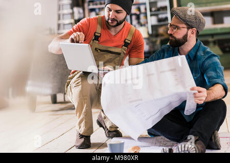 Two men with tablet looking and draft sitting on the floor - Stock Photo