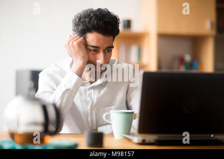 Portrait of businessman at desk looking at laptop - Stock Photo