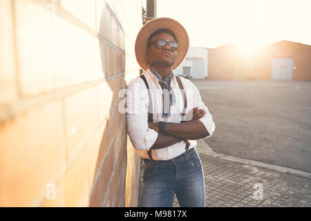 Portrait of cool young man wearing hat and sunglasses leaning against wall - Stock Photo