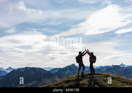 Austria, Tyrol, young couple standing in mountainscape cheering - Stock Photo