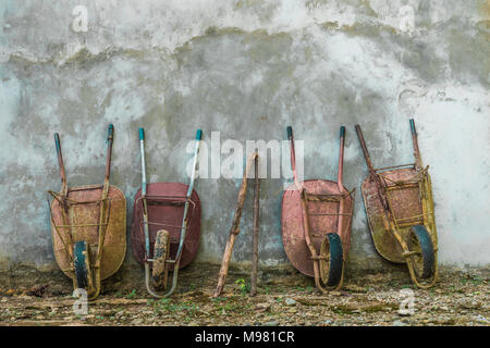 Four old wheelbarrows leaning against wall - Stock Photo