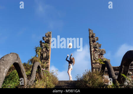 Indonesia, Bali, young woman throwing her hat in the air - Stock Photo